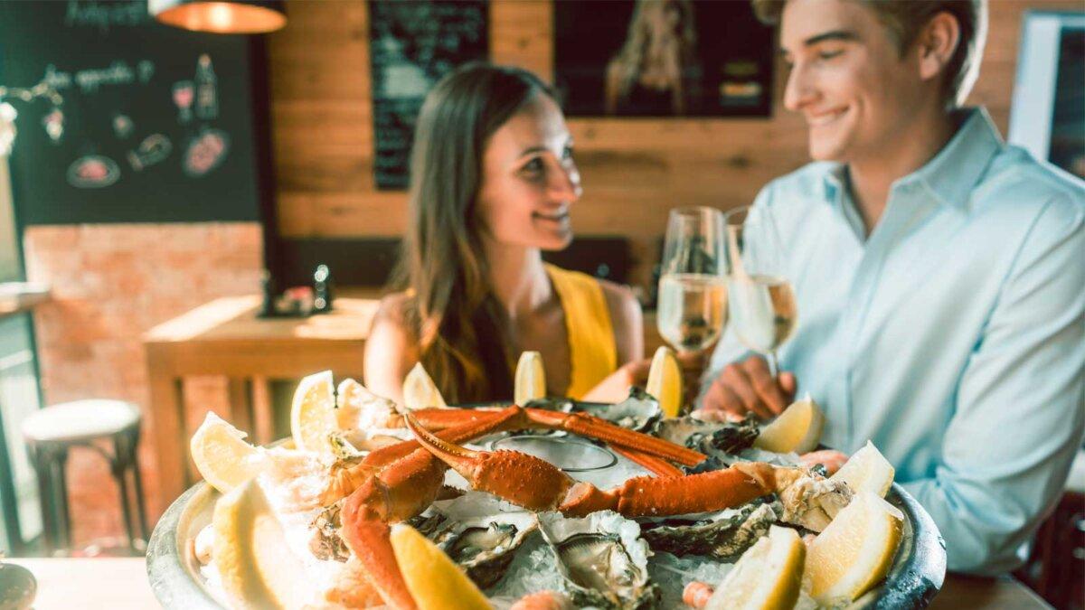 Молодая пара едят морепродукты