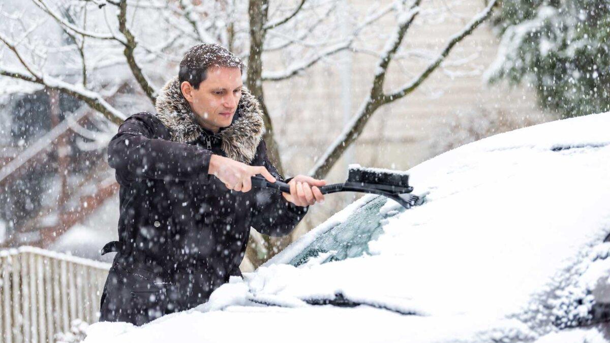 Мужчина чистит машину от снега man cleaning car windshield from snow