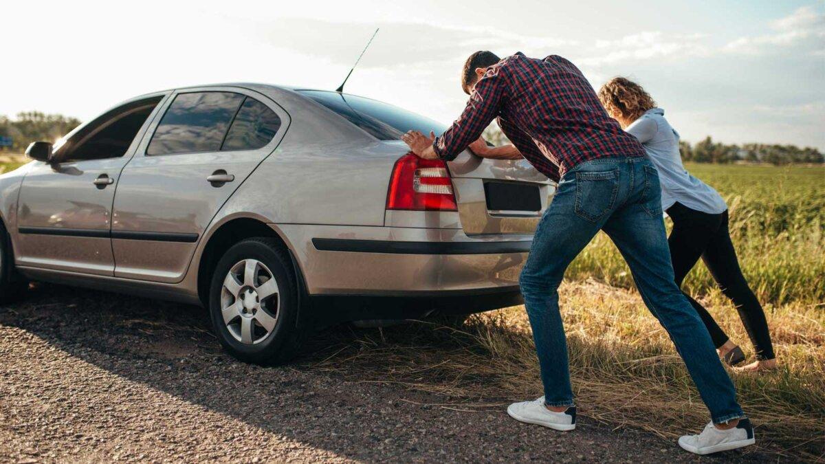 Мужчина и женщина толкая сломанный автомобиль, вид сзади