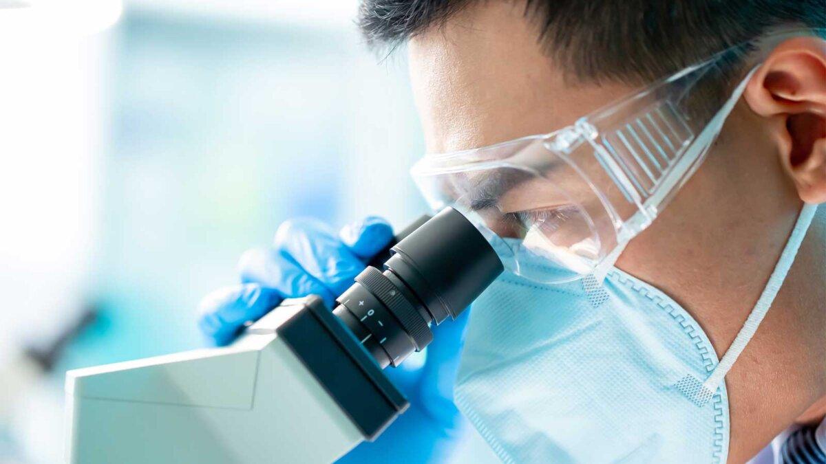 Мужчина микробиолог в маске проводит исследования в лаборатории microbiologist biotechnology researcher or medical worker look microscope in the lab