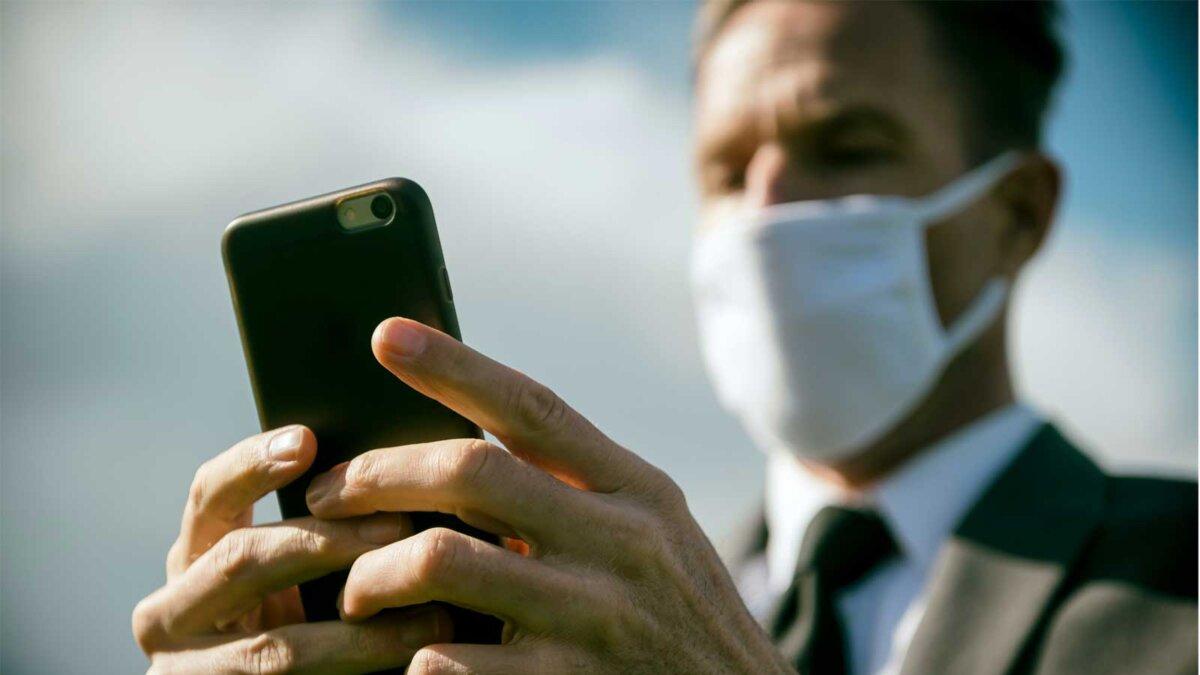 Мужчина в костюме и маске с телефоном Worried businessman wearing surgical face mask checking his smartphone