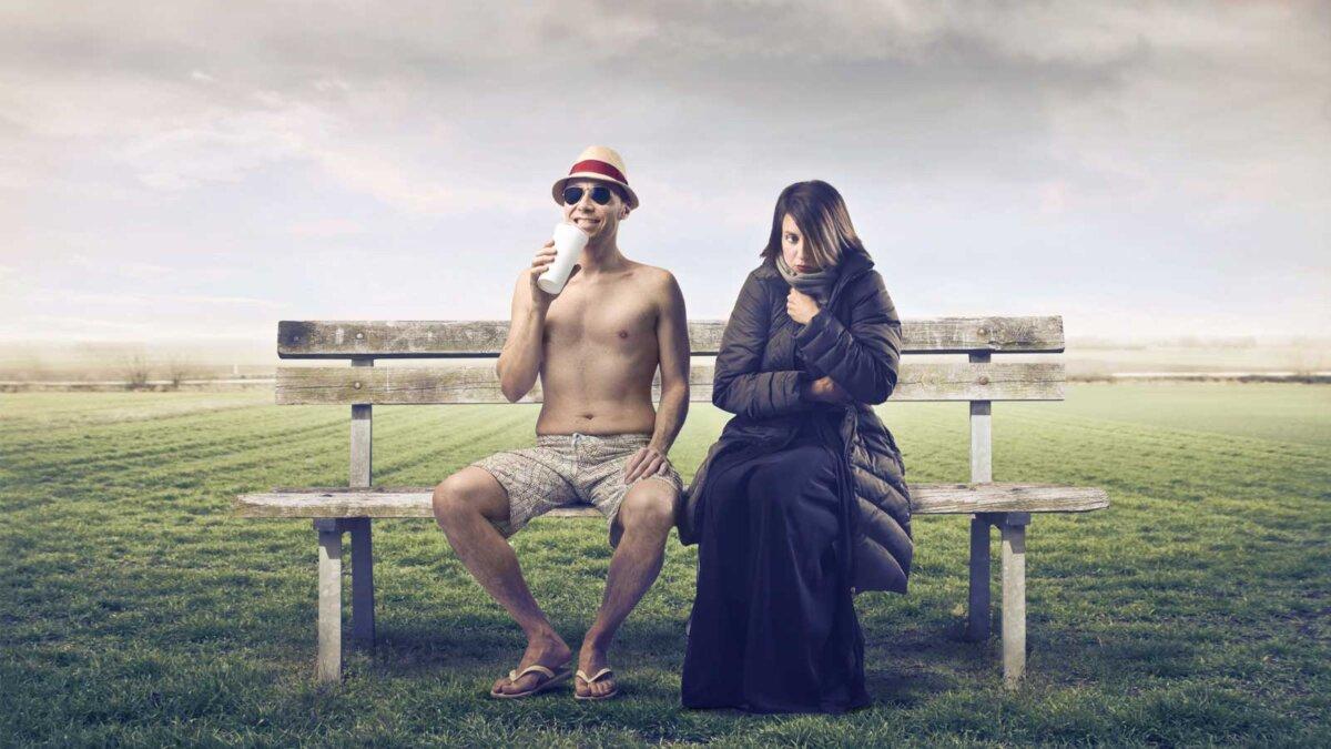 Мужчина в летней одежде сидит на скамейке в парке с женщиной, завернутой в теплую одежду рядом с ним