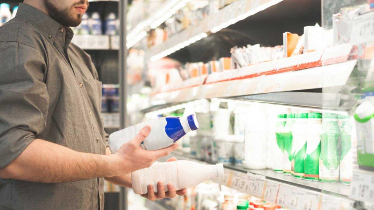 Мужчина выбирает молоко в молочном отделе