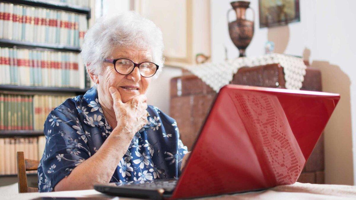 Пожилая женщина сидит дома за компьютером Surprised senior woman looking at laptop