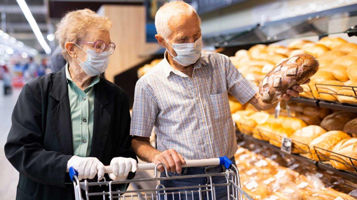 Пожилые люди в магазине покупают хлеб в масках