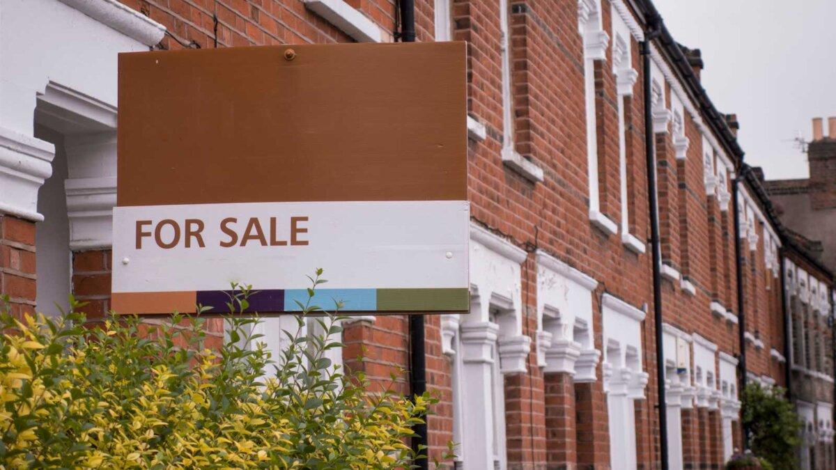 Ряды домов из красного кирпича с табличкой на продажу в Лондоне