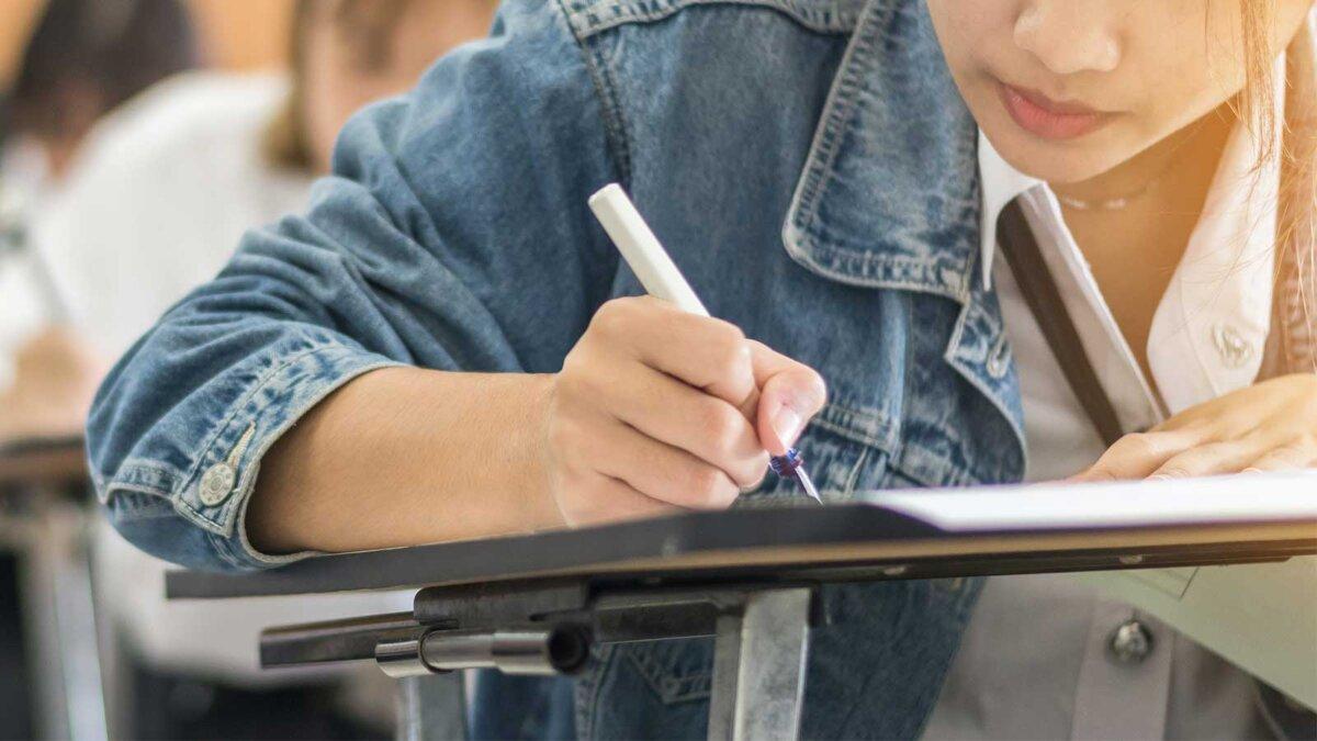 Сдача школьником экзамена написание ответа в классе для вступительного экзамена