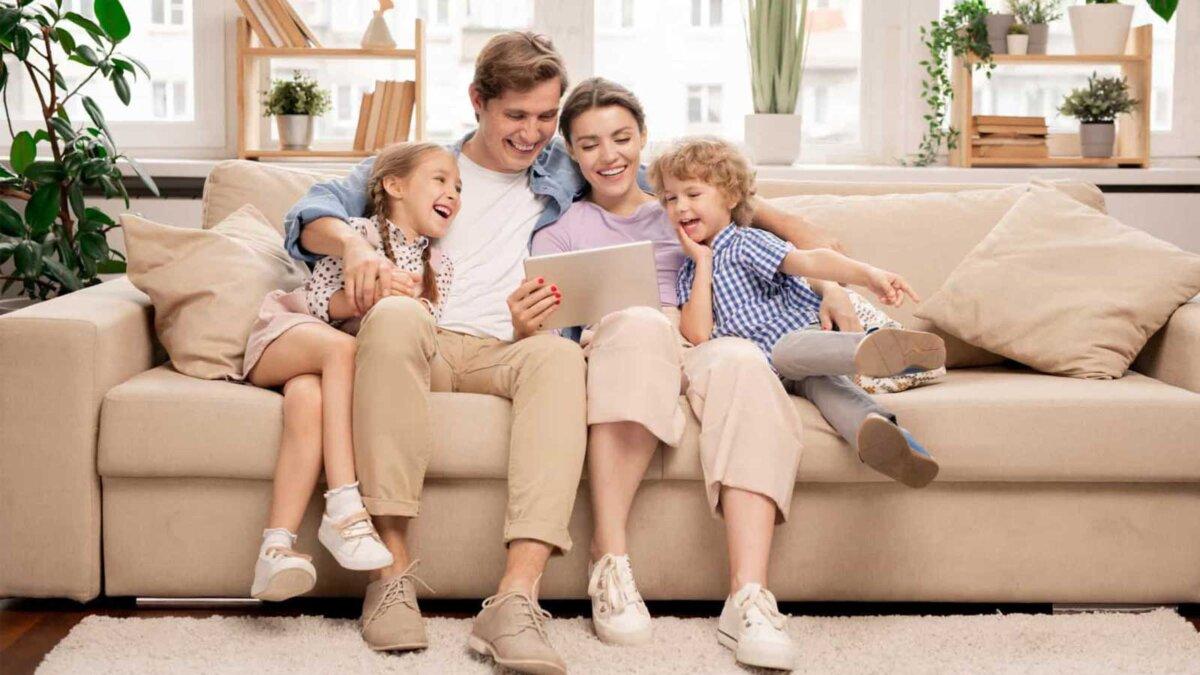 Семья на диване смотрят фильм Young joyful casual family of two kids and couple sitting on sofa and watching funny video