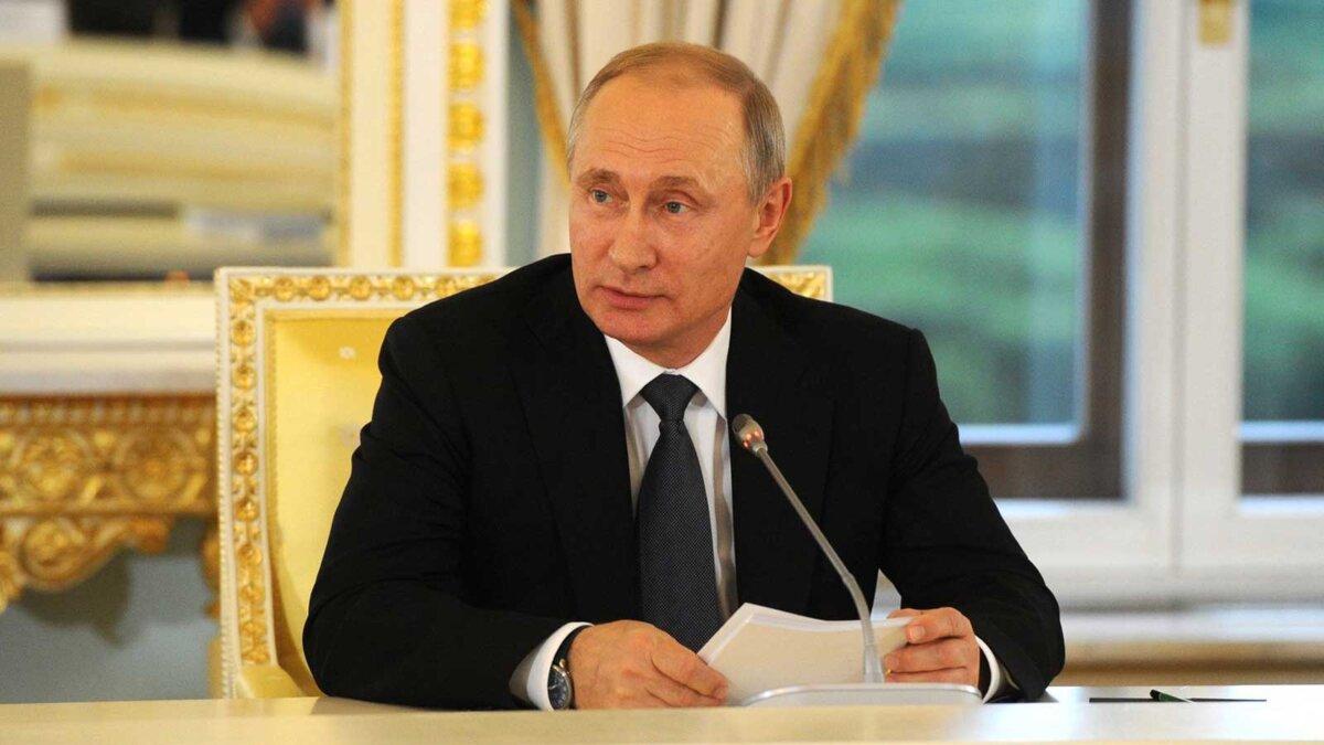 Владимир Путин сидит за столом бумаги микрофон