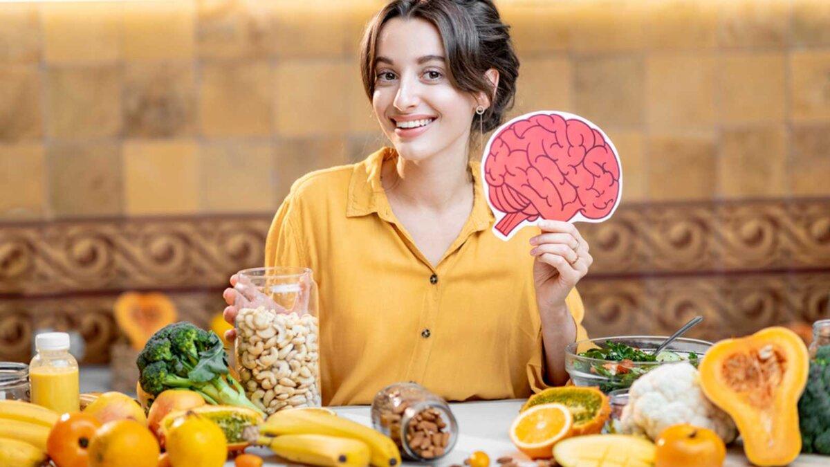 Woman holding human brain model with variety of healthy fresh food on the table продукты для мозга тыква женщина за столом