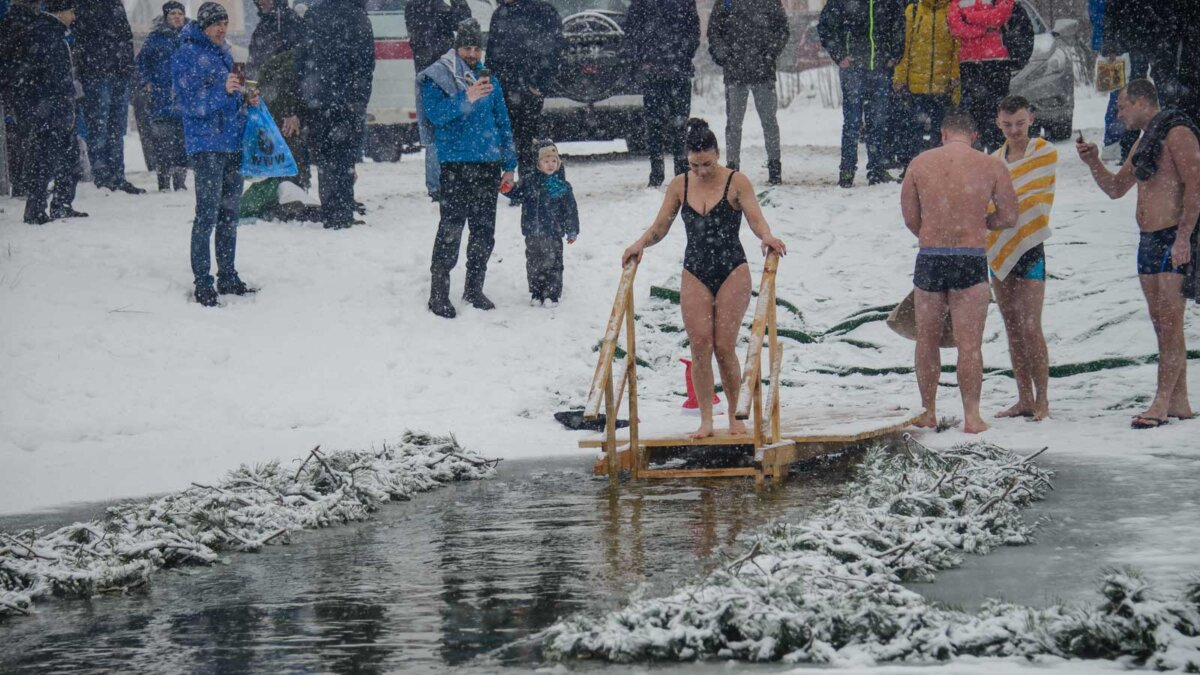 Женщина спускается люди крещенские купания A woman stands near the hole
