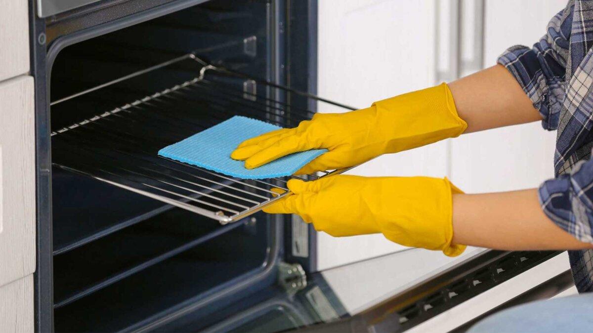 Женские руки в перчатках моют духовку wash the oven