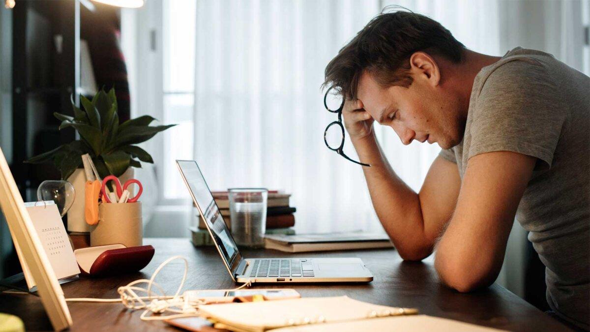 человек стресс за столом во время работы на ноутбуке