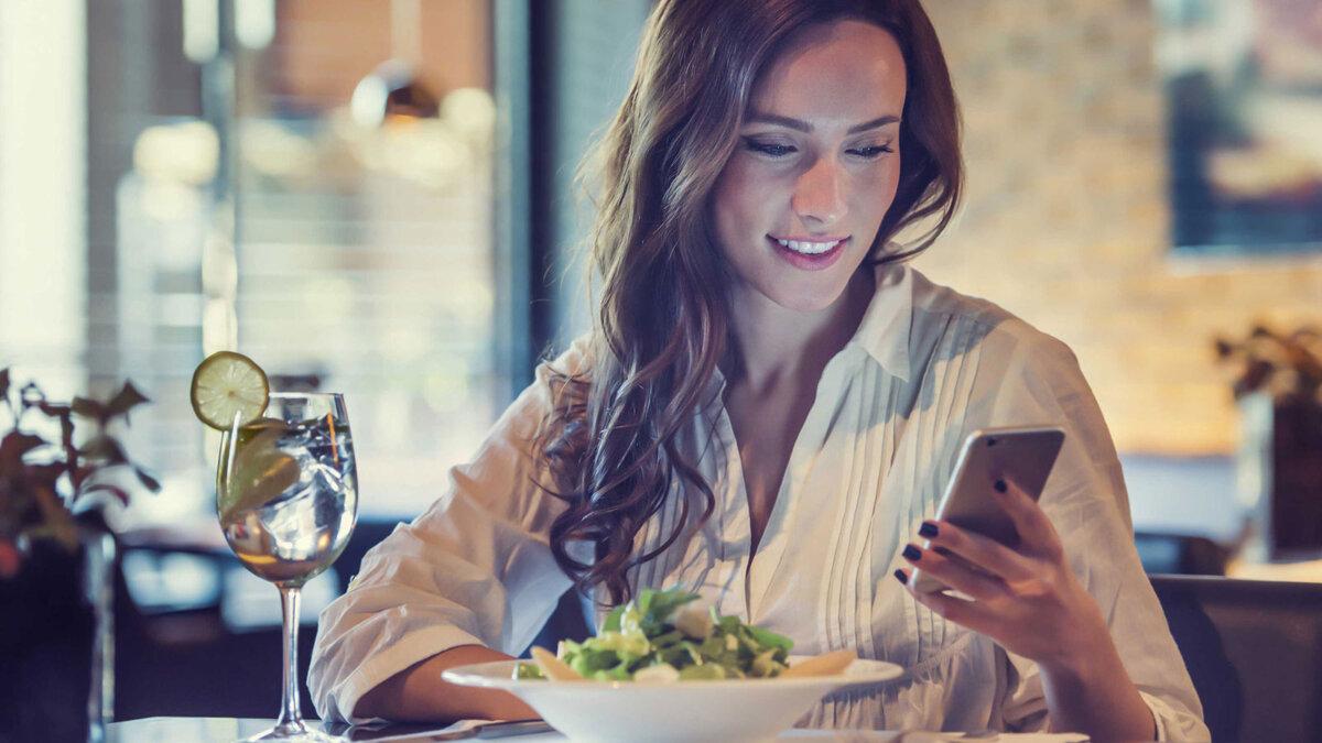 девушка ест со смартфоном в руках