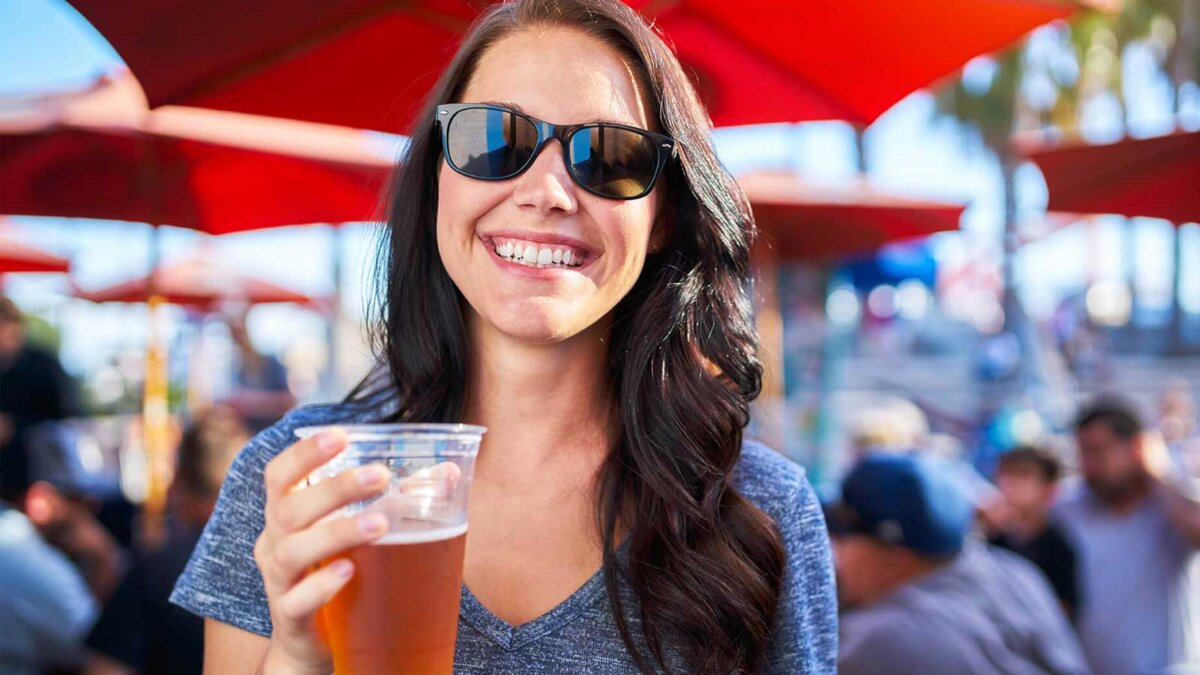 девушка улыбается стакан пива woman with plastic cup of beer at outdoor bar or pub