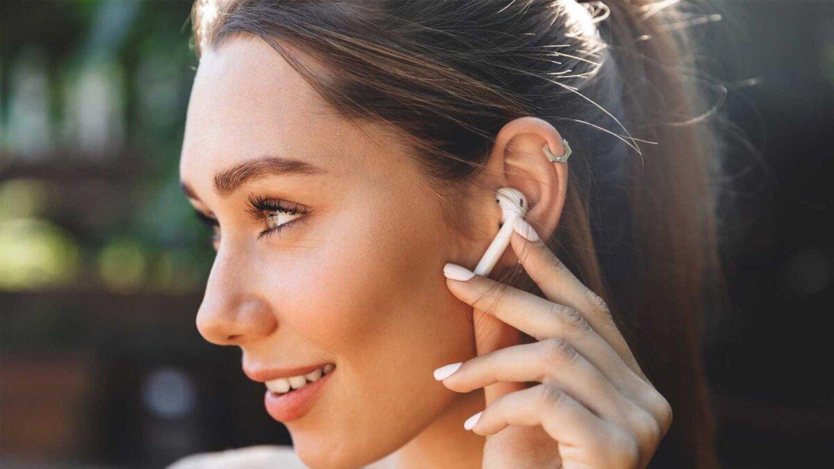 молодая фитнес девушка слушает музыку через беспроводные наушники на открытом воздухе