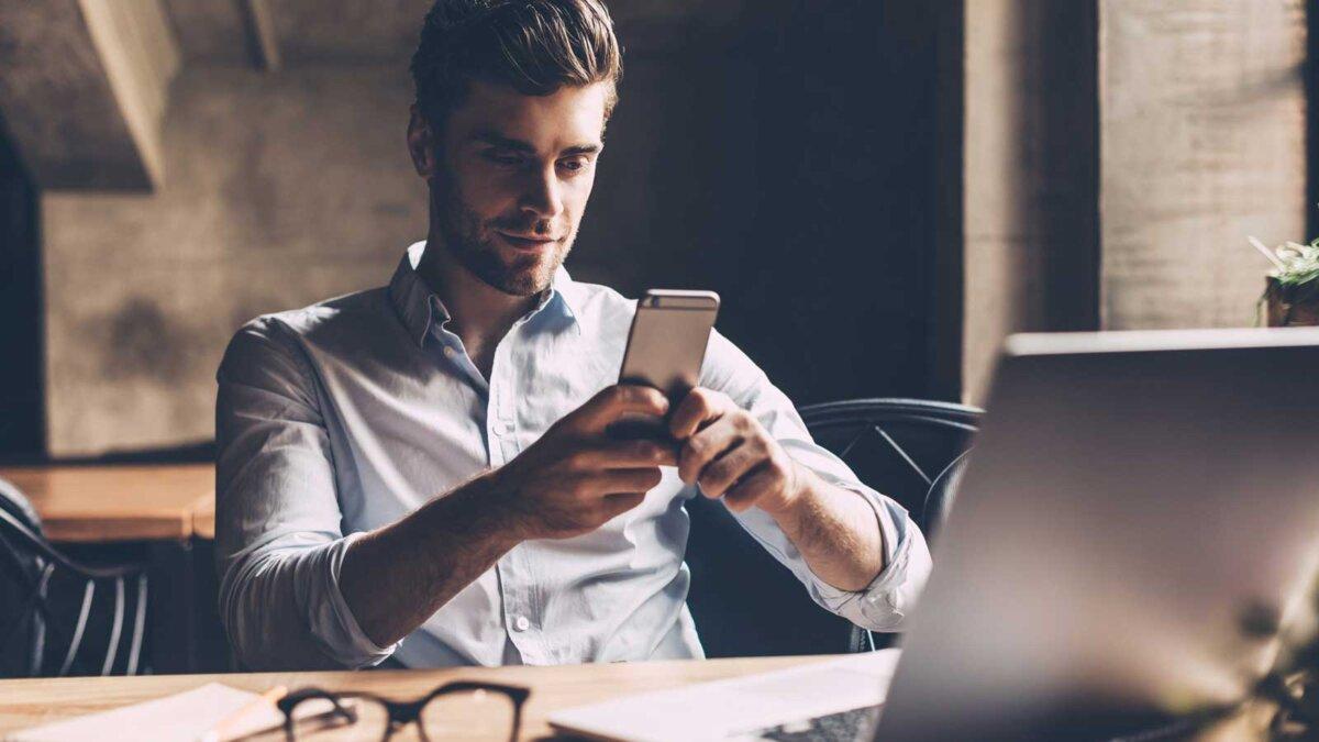 молодой человек сидит с телефоном за столом компьютер очки