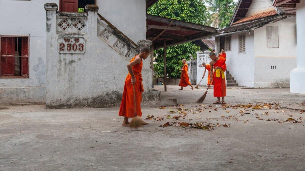 Буддийские монахи с мётлами подметают