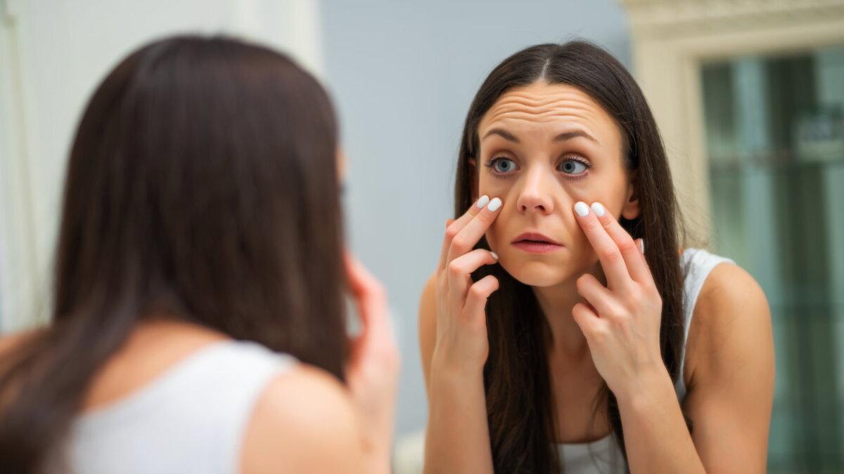 Девушка рассматривает глаза веки в зеркале