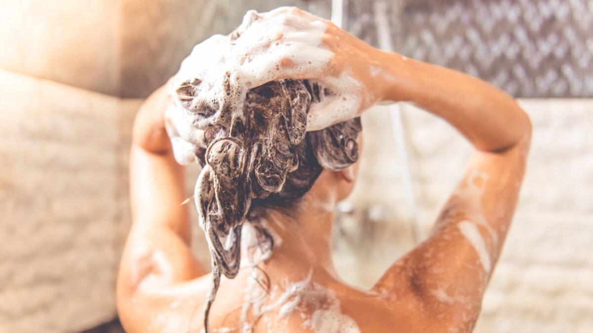 Женщина моет голову шампунем