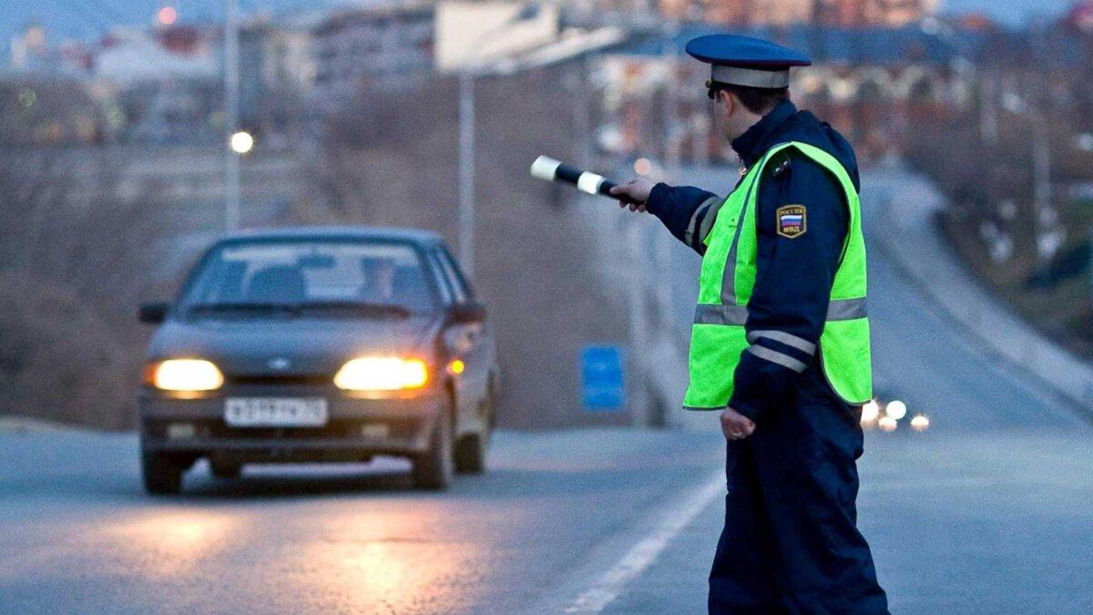 сотрудник ДПС останавливает автомобиль на дороге