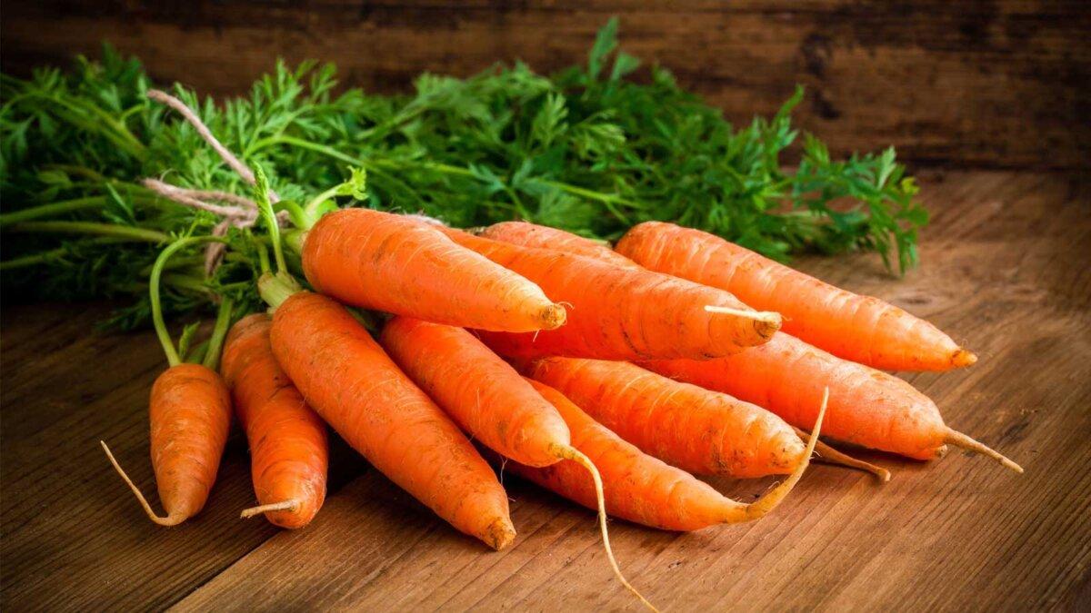свежая морковь куча на деревенском деревянном фоне