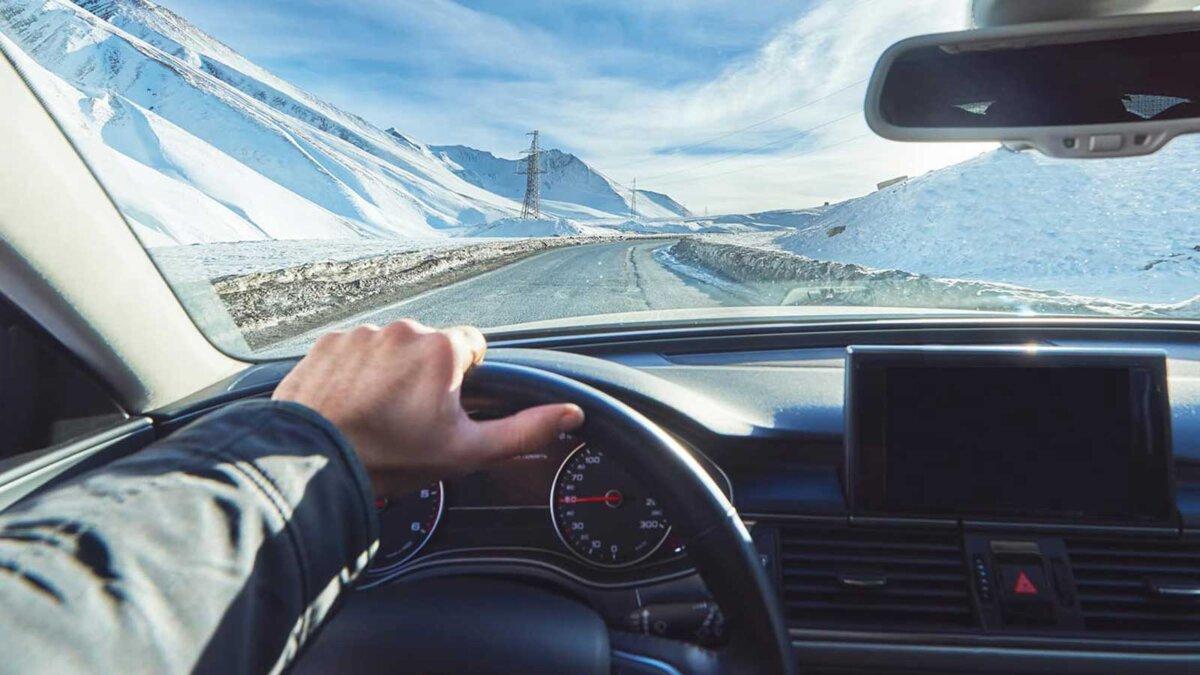 вид из автомобиля внутри с частью внутреннего экрана gps с водителем мужской рукой на руле во время яркого снежного солнечного дня на прямой ледяной дороге с заснеженными горами