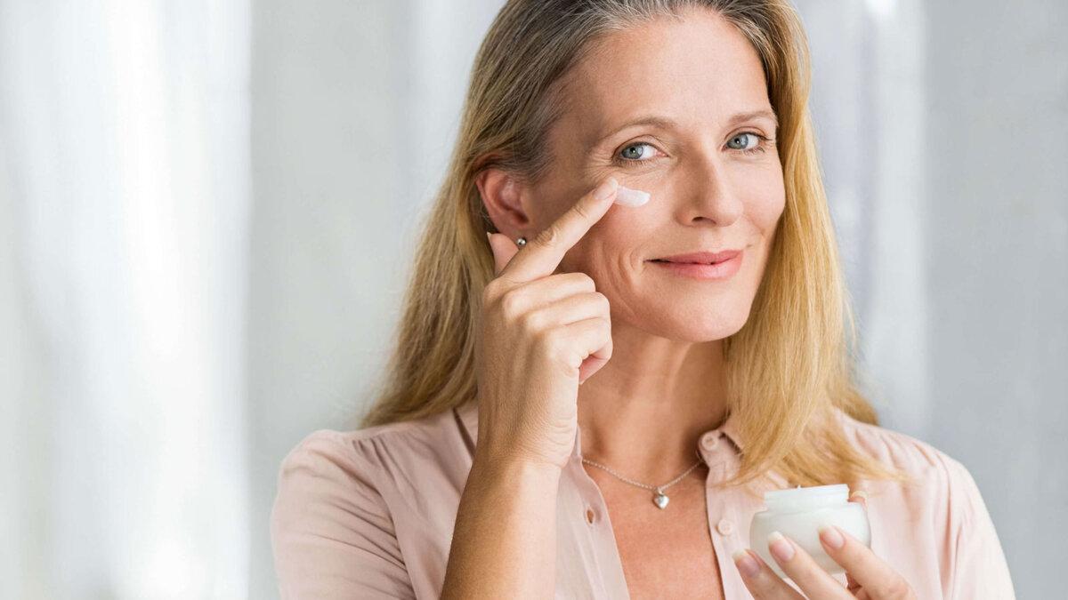 женщина мажет кремом под глазами