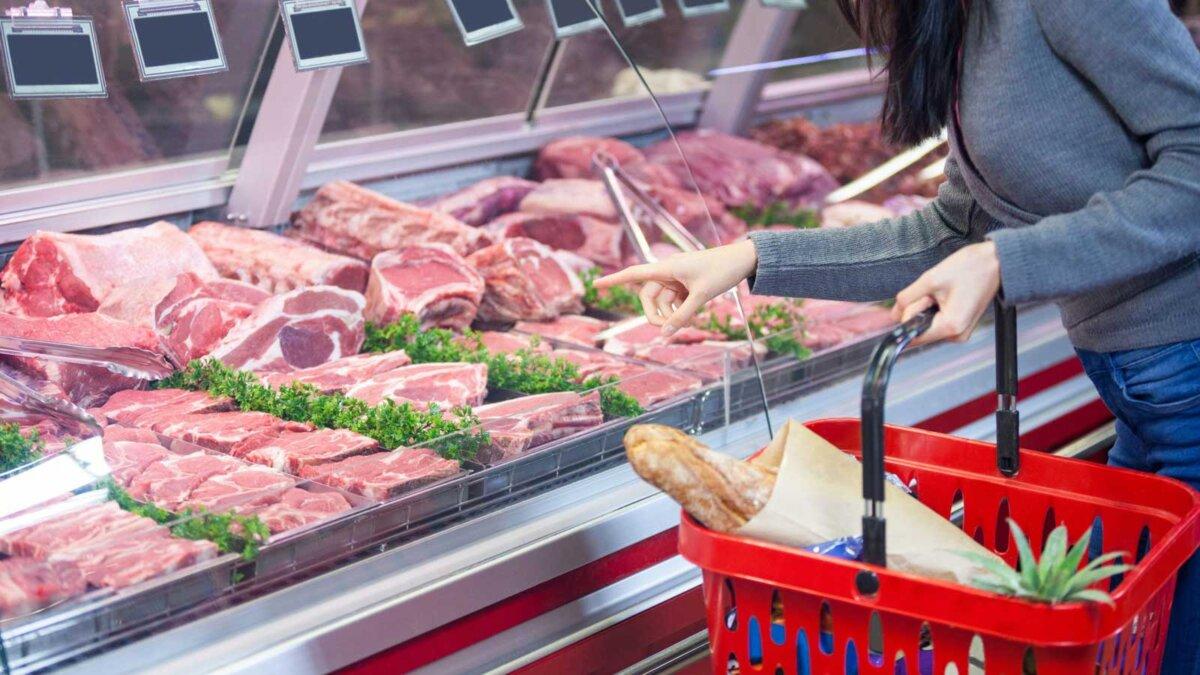женщины, указывая на мясо на дисплее в супермаркете