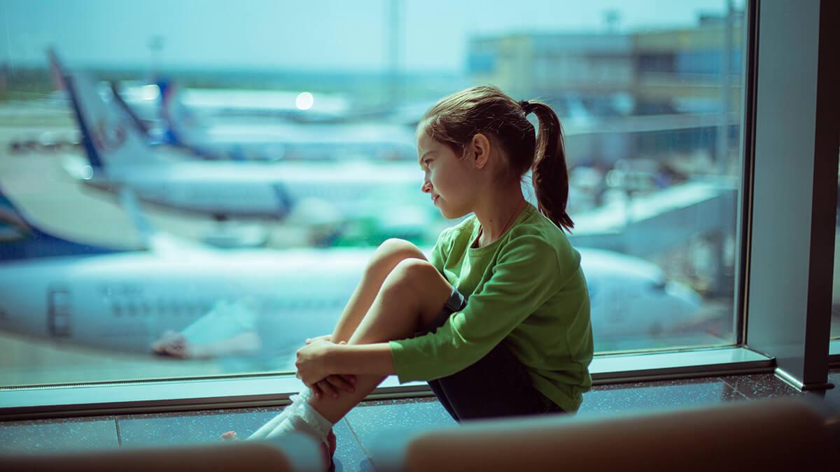 Ребенок у окна в аэропорту.