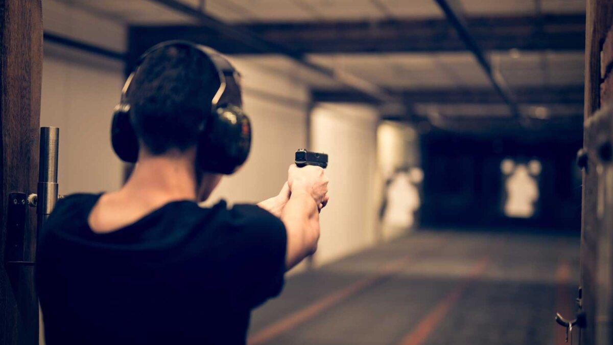 Человек прицеливания пистолета в цель в помещении полигона или стрельбище