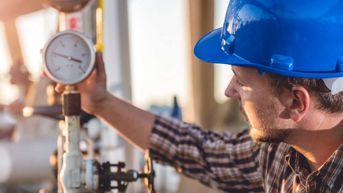 Человек, проверяющий манометр на заводе природного газа