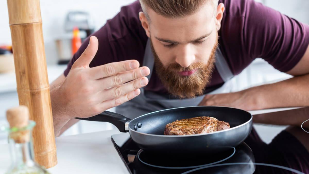 Мужчина готовит мясо стейк