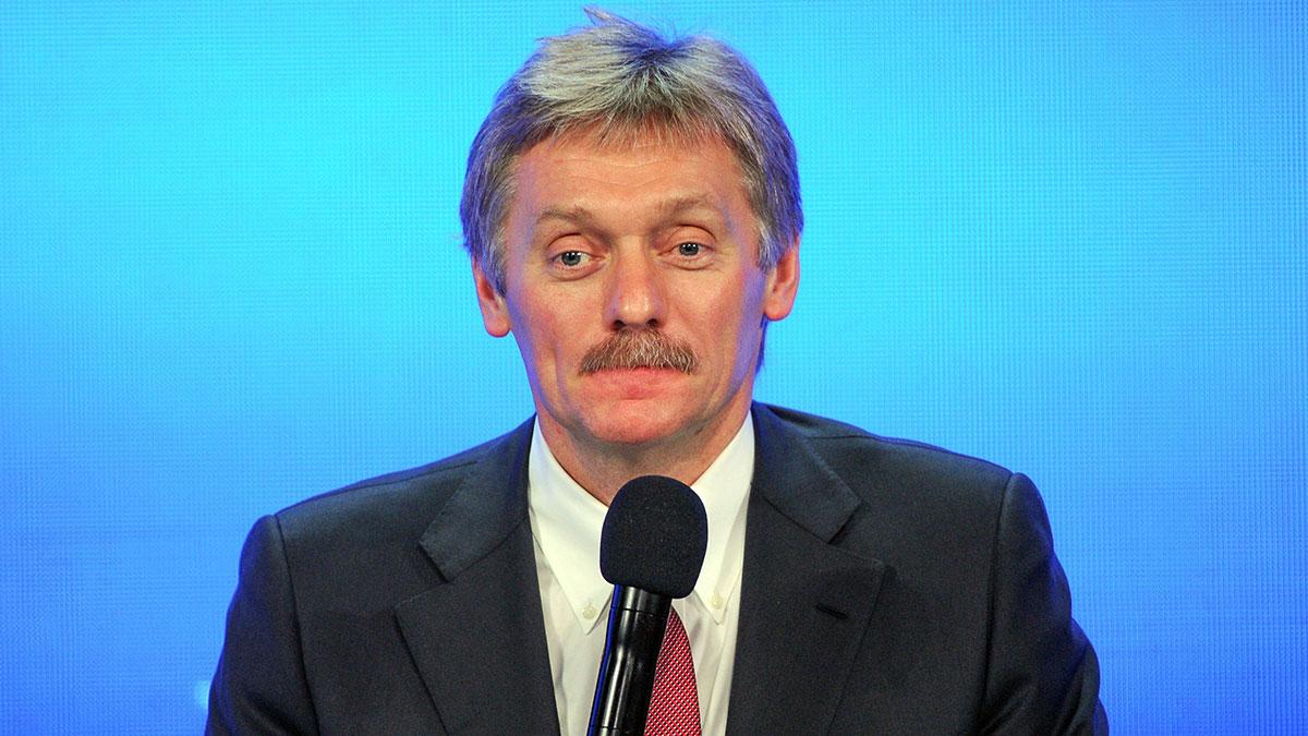 Дмитрий Песков пресс-секретарь президента Российской Федерации на синем фоне микрофон