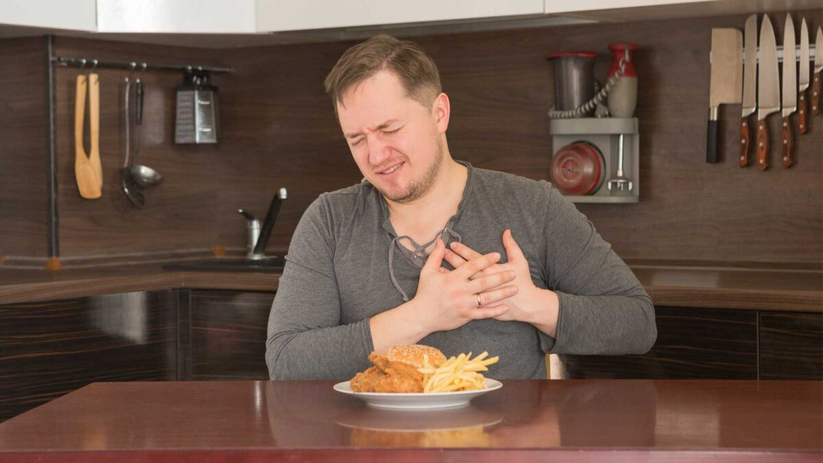 Мужчина на кухне вредная пища болит сердце