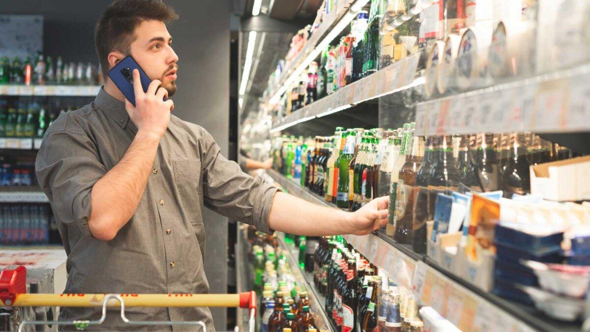Мужчина покупает пиво в магазине и говорит по телефону