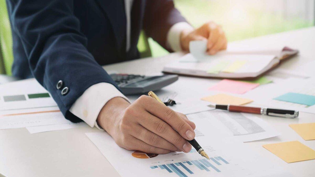 Мужчина в костюме калькулятор ручка документы