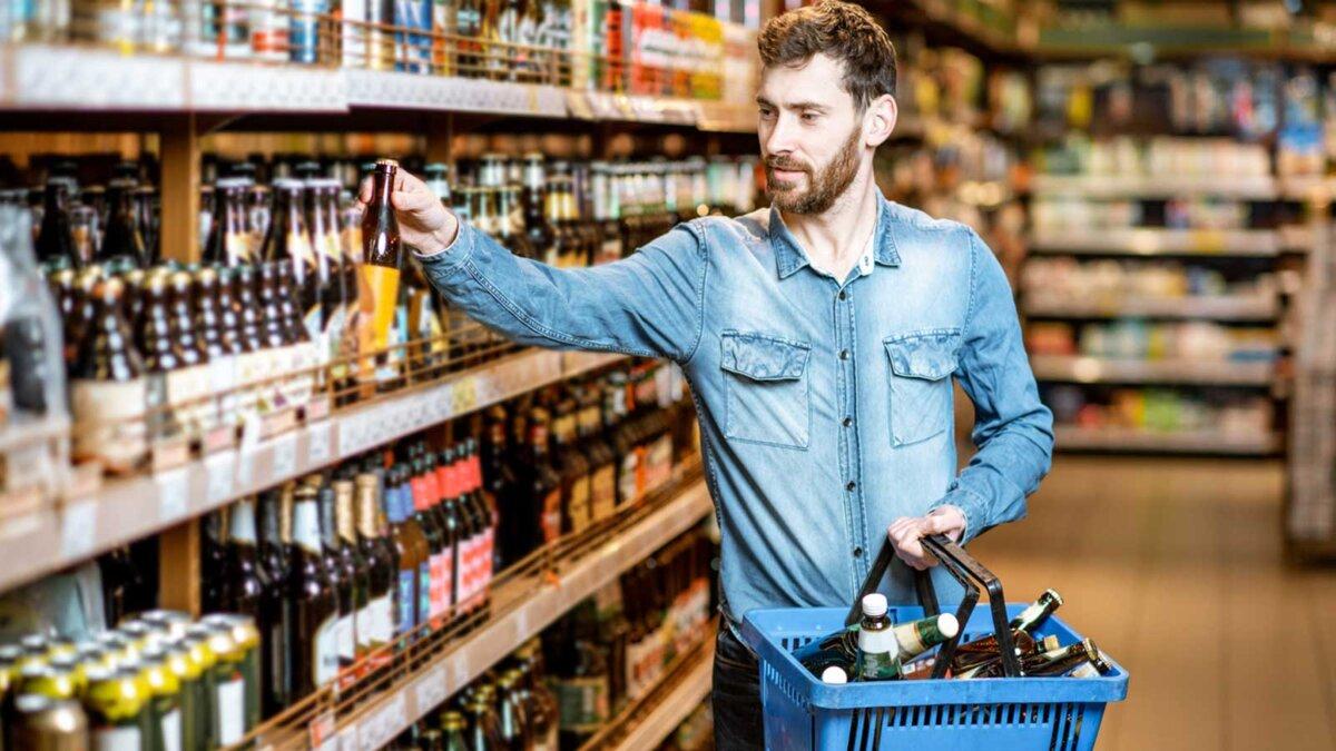 Мужчина в магазине покупает много пива