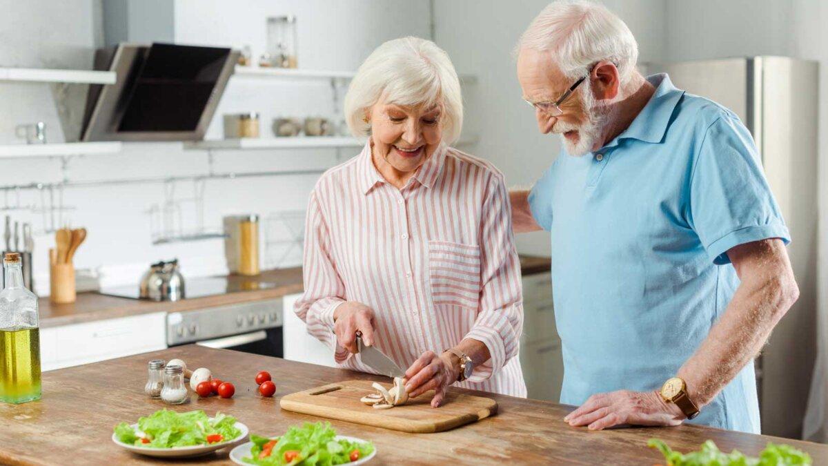 Пожилая пара режет помидоры грибы