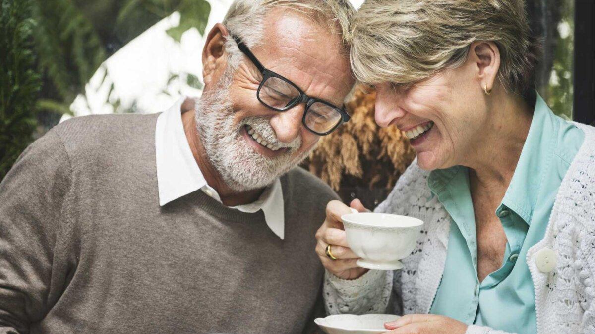 Пожилая пара пьет чай и смеются