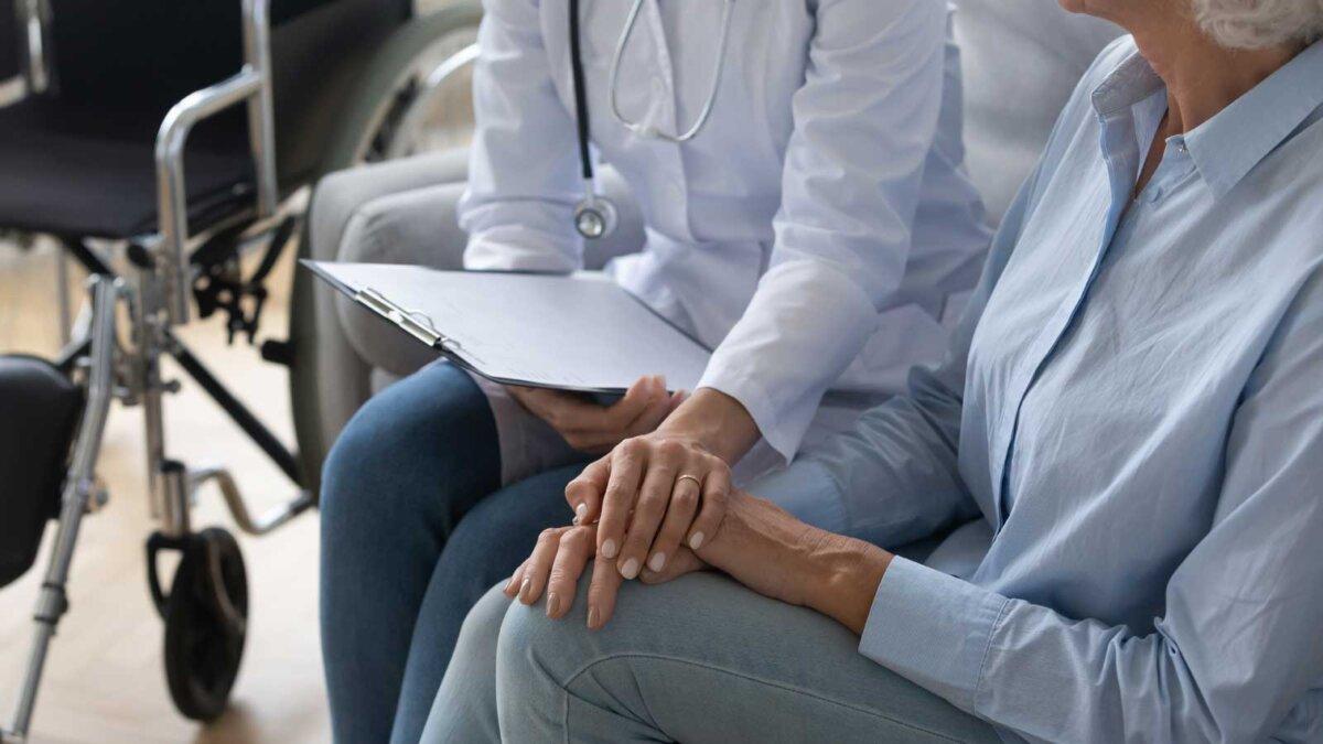 Пожилая женщина на приеме у врача инвалидное кресло