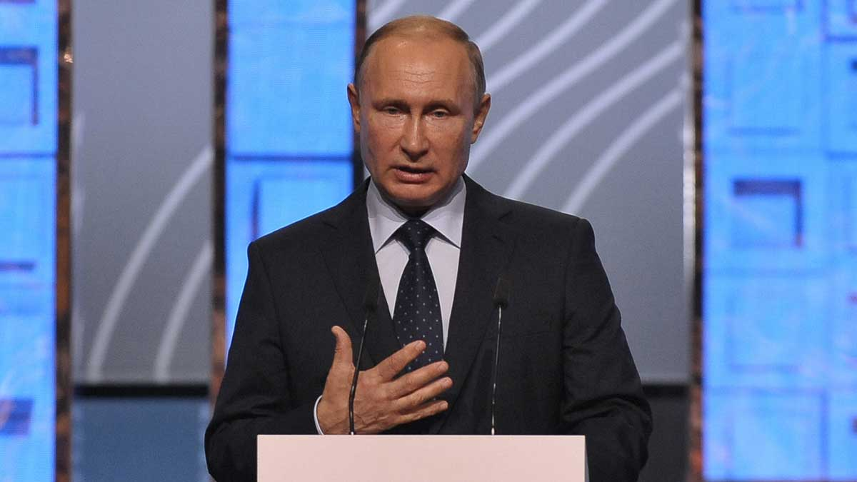 Президент России Владимир Путин поднимает руку