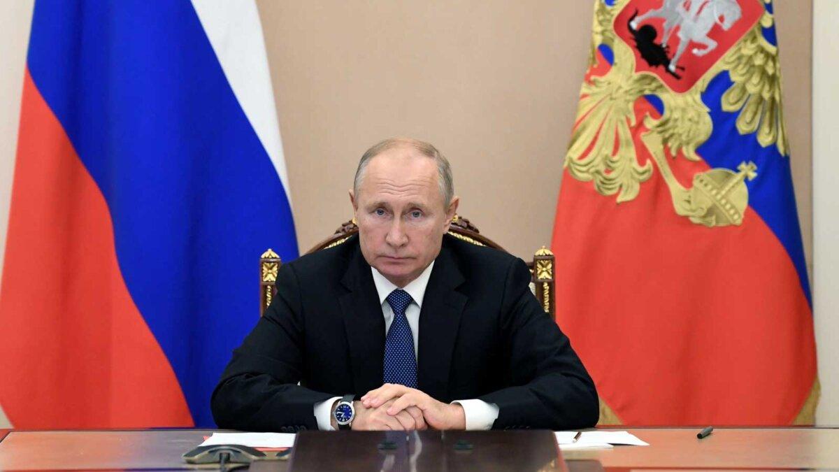Владимир Путин за столом на фоне флагов