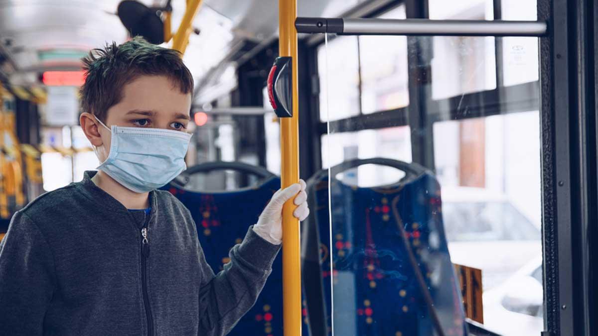 мальчик в маске держится за поручень в автобусе
