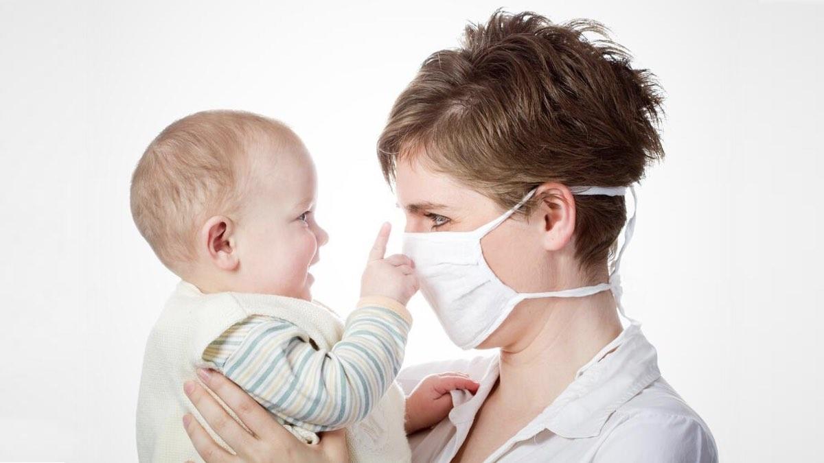 мать в маске с новорожденным