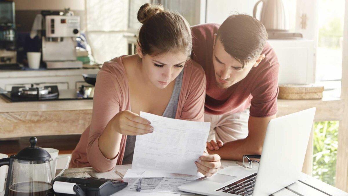 мужчина и девушка изучают квитанцию ноутбук