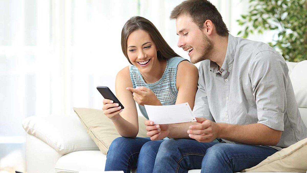 парень и девушка смотрят на телефон и улыбаются