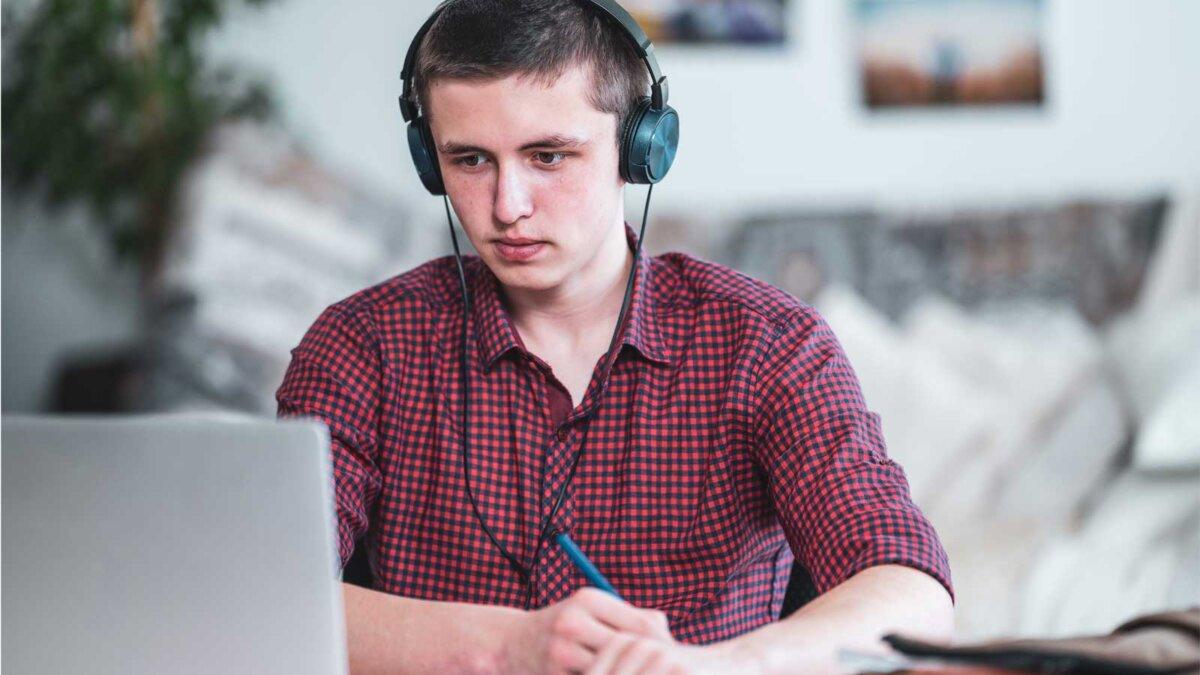 парень наушники ноутбук за столом ручка