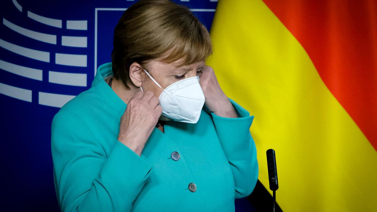 канцлер Германии ангела Меркель в маске на фоне флага