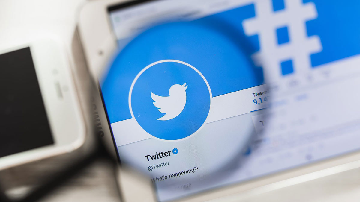 социальная сеть twitter на экране планшета лупа